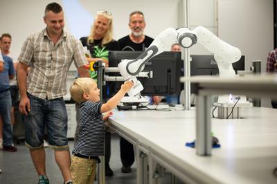 Auch kleine Besucher konnten erfahren, wie man einen kollaborierenden Roboter von Hand bewegt. Bei dem Roboter handelt es ich den Cobot Panda der Firma Franka Emika.