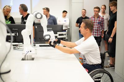 Besucher konnten erfahren, wie man einen kollaborierenden Roboter von Hand bewegt.