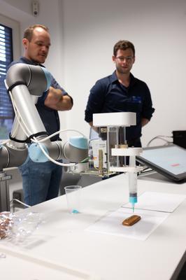 Mithilfe eines Universal Robots UR5 Roboters konnten Namen mit Zuckerguss auf Printen gedruckt werden. Die Eingabe des Namens erfolgte dabei über einen Touchscreen, nach der Eingabe wurde der Schriftzug in ein entsprechendes Fahrprofil für den Roboter umgewandelt.